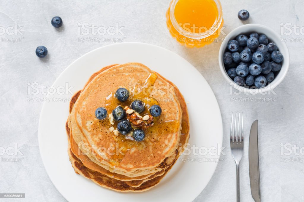 Pancakes with blueberries, honey and walnuts stock photo