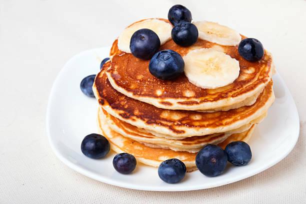 pfannkuchen mit blaubeeren und bananen - gebackene banane stock-fotos und bilder