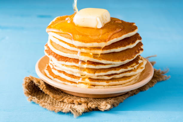 pancakes with butter and honey on blue wooden table. - pancake foto e immagini stock