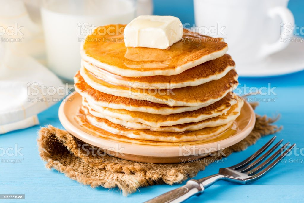 Hot Cakes con mantequilla y miel en la mesa de madera azul. - Foto de stock de Al horno libre de derechos