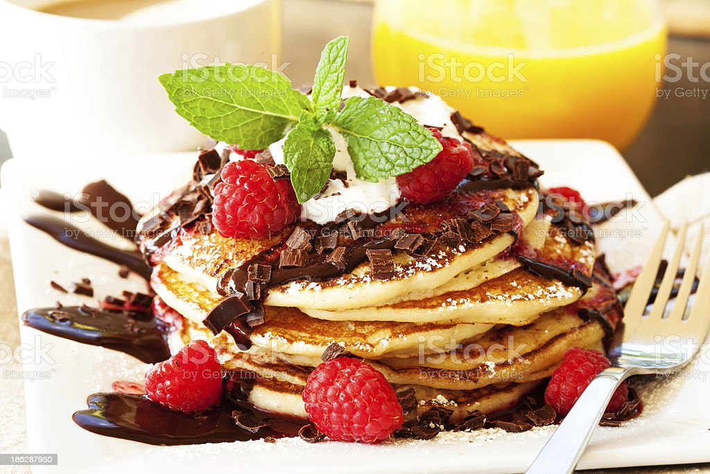 Pancakes with chocolate sauce and raspberries royalty-free stock photo