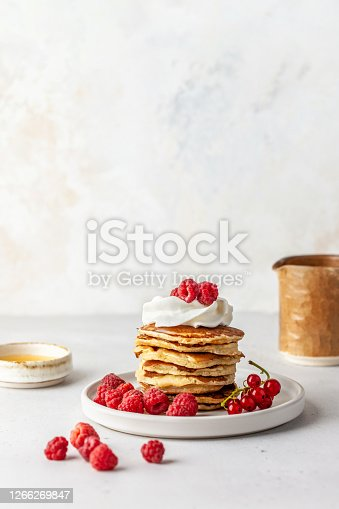 Breakfast. A stack of pancakes on a plate, honey and milk jug on the table