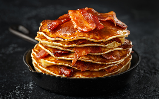istock Pancakes with crispy bacon and maple syrup in cast iron skillet, frying pan. Morning Breakfast 1132724782