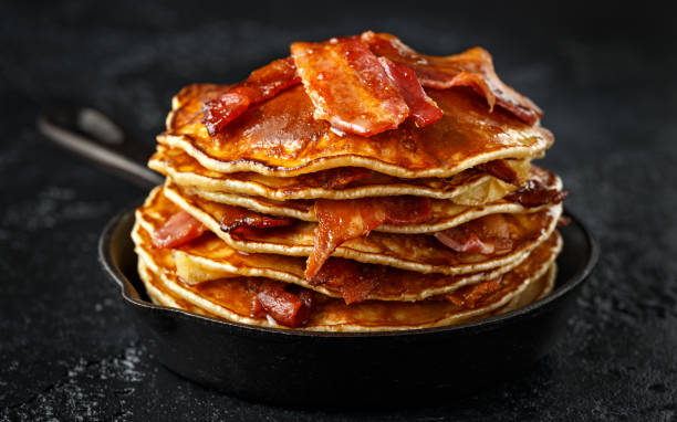 Pancakes with crispy bacon and maple syrup in cast iron skillet, frying pan. Morning Breakfast Pancakes with crispy bacon and maple syrup in cast iron skillet, frying pan. Morning Breakfast. Anglo American stock pictures, royalty-free photos & images