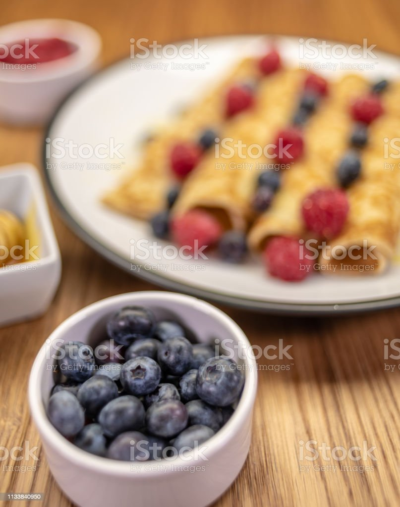 Pancakes with honey, raspberries and blueberries stock photo