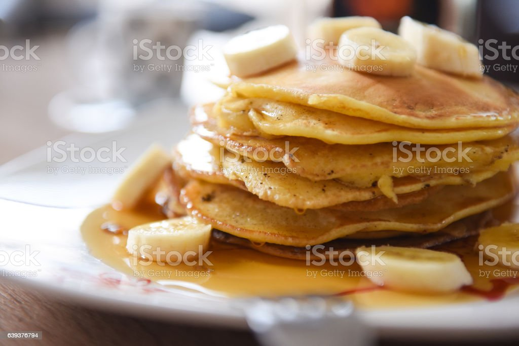Pancakes with maple syrup and bananas. stock photo