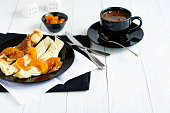 pancakes with peach jam in a black bowl on a white wooden background. delicious breakfast with coffee