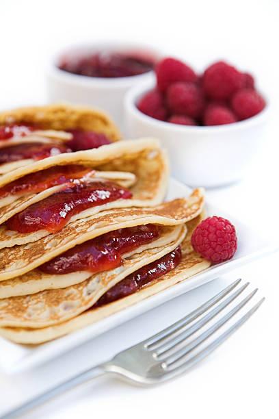 Pancakes with raspberry jam & fresh raspberries stock photo