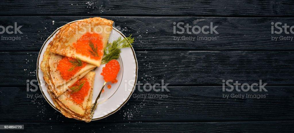 Crêpes au caviar rouge sur une plaque. Sur un fond en bois. Vue de dessus. Espace libre pour le texte. - Photo