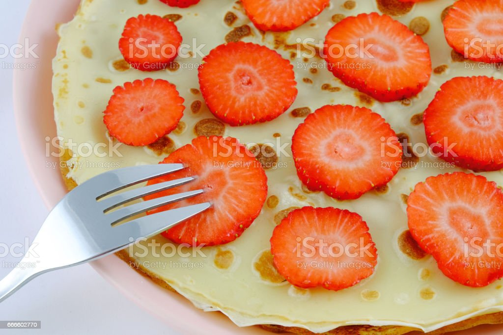 Pancakes with slices of strawberries. stock photo