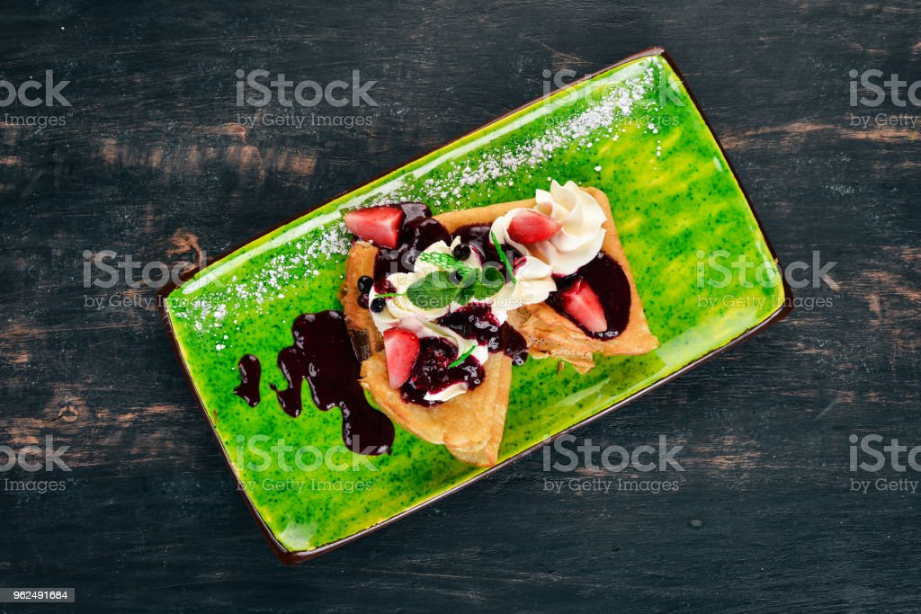 Pancakes with strawberries and berry jam. On a black wooden background. Copy space. - Royalty-free Baked Stock Photo