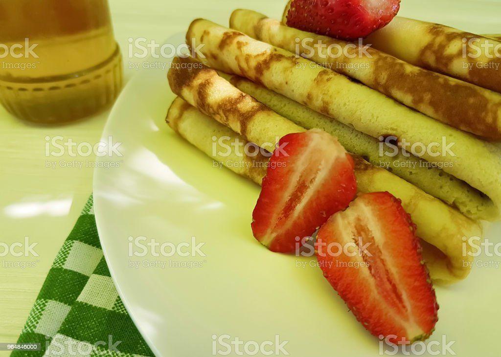 pancakes with strawberries honey on white wooden, fork, towel royalty-free stock photo