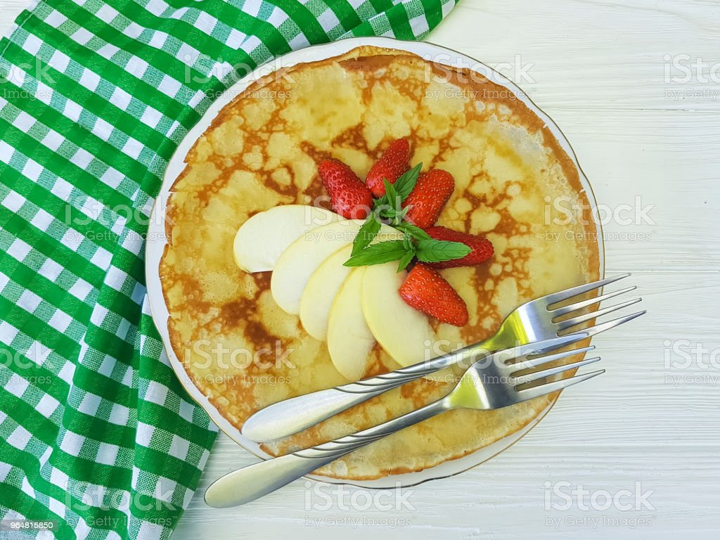 pancakes with strawberry apple mint on white wooden, fork, towel stock photo