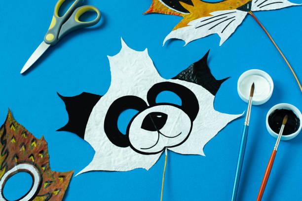 Panda mask painted on maple leaf stock photo
