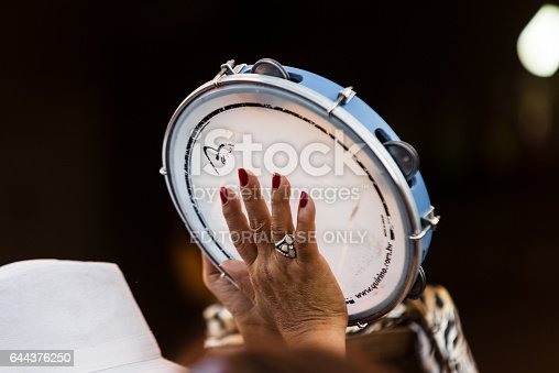 Conservatoria (Rio de Janeiro), Brazil - July 09, 2013: Woman playing tambourine during a performance of Mulheres de Aquilah (portuguese for Women of Aquilah) samba group presentation on the streets of historic viallage. The group is formed exclusively by women percussionists and is based in Madureira, popular samba neighborhood in Rio de Janeiro capital.