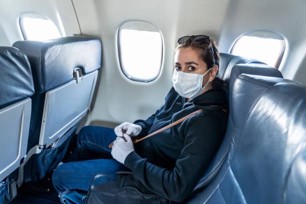 COVID-19 Grenzschließungen von Pandemie. Junge Frau im Flugzeug, die in ihre Heimatstadt zurückkehrt, nachdem sie in einem fremden Land festsitzen, da die Regierungen die Reise eingeschränkt haben, um die Ausbreitung des Coronavirus zu stoppen. – Foto