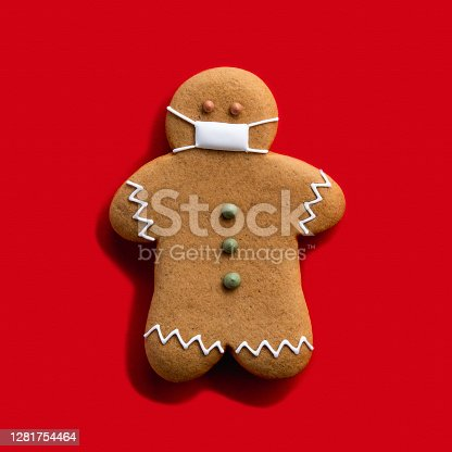 Pandemic Christmas. Quarantine celebration. Covid-19 winter holidays. Brown gingerbread man in protective face mask alone isolated on red background.