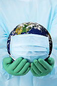 A DSLR photo of doctor's hands in gloves holding the planet Earth in a medical mask. Space for copy. Earth globe image provided by NASA - https://visibleearth.nasa.gov/view.php?id=54388