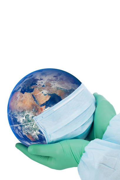 Pandemic concept - doctor's hands in gloves holding the planet Earth in a medical mask (Eastern hemisphere) stock photo
