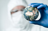 Pandemic concept, close up of scientist holdnig and analyzing planet earth