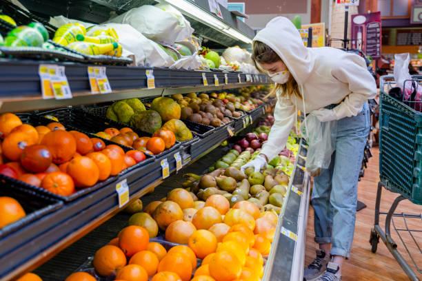 Pandemie Zeiten Einkaufen. Eine junge Frau mit Schutzmaske und Handschuhen, die in einem Supermarkt Früchte kauft. – Foto