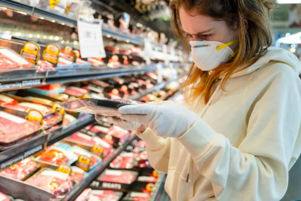 Pandemie Zeiten Einkaufen. Eine junge Frau mit Schutzmaske und Handschuhen, die in einem Supermarkt Fleisch kauft. – Foto