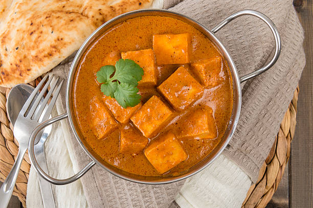 Paneer Makhani soup sitting on a towel Shahi Paneer (Paneer Butter Masala) - Indian curd cheese curry in a balti dish, served with naan bread and garnished with coriander leaves. balti dish stock pictures, royalty-free photos & images