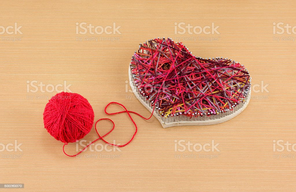 Panel of heart shaped made of thread and nails and clew of thread
