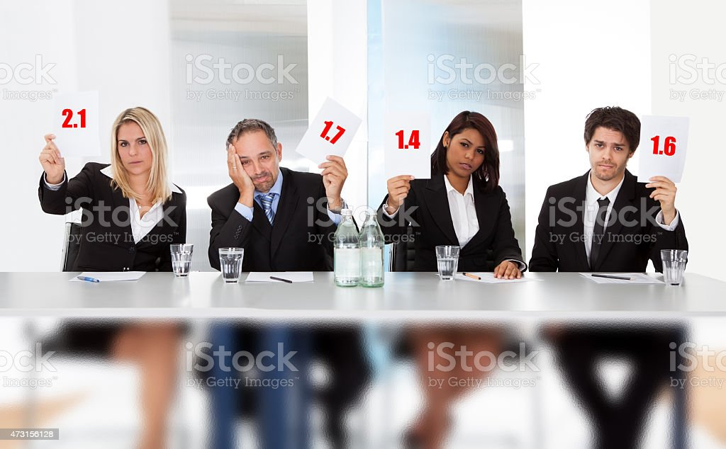 Panel judges holding bad score signs stock photo