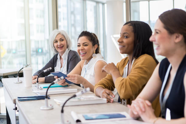 A panel of women present information A diverse panel presents information at the yearly university women's conference. college fair stock pictures, royalty-free photos & images