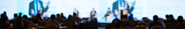 Panel on Stage during Discussion Event. Debate with Experts during Conference Seminar Presentation. Successful Executives and Entrepreneur Speakers and Presenters in Conference Hall Lecture Series. Blurred panel and presenter hands up, and blurred audience debate stock pictures, royalty-free photos & images