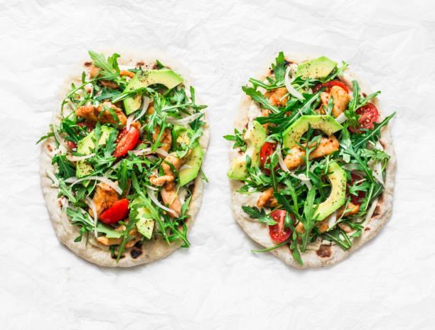 schweinebraten fladenbrot huhn, avocado, tomaten, rucola-pizza auf heller kulisse, top-aussicht - fladenbrotpizza stock-fotos und bilder
