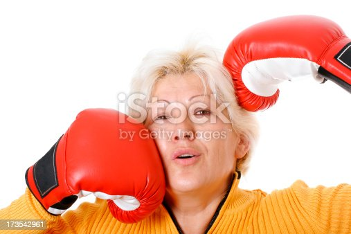 Metaphorical situation - middle-aged woman in boxing gloves hitting herself