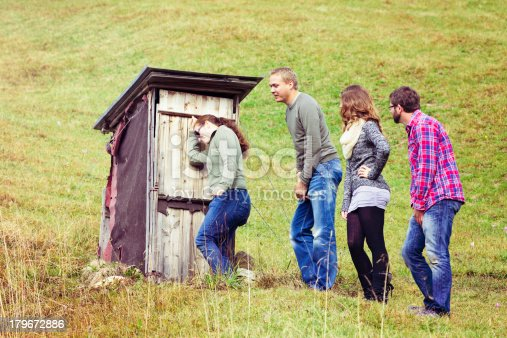 Four tourists are painfully waiting for their turn to go by a small outhouse.
