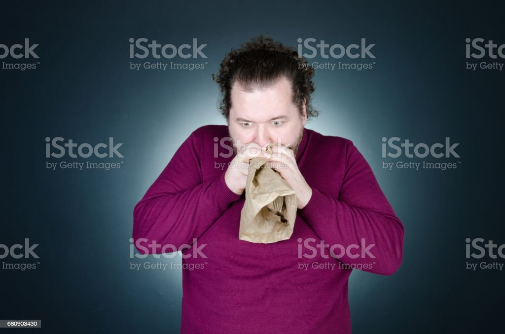 Panic attack. A man is holding a paper bag. stock photo