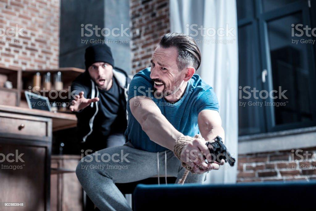 Ladrão de pânico tentando tirar a arma - foto de acervo