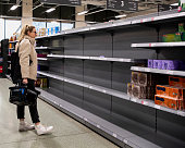 A young Caucasian female stands looking concerned at the empty shelves in a supermarket.