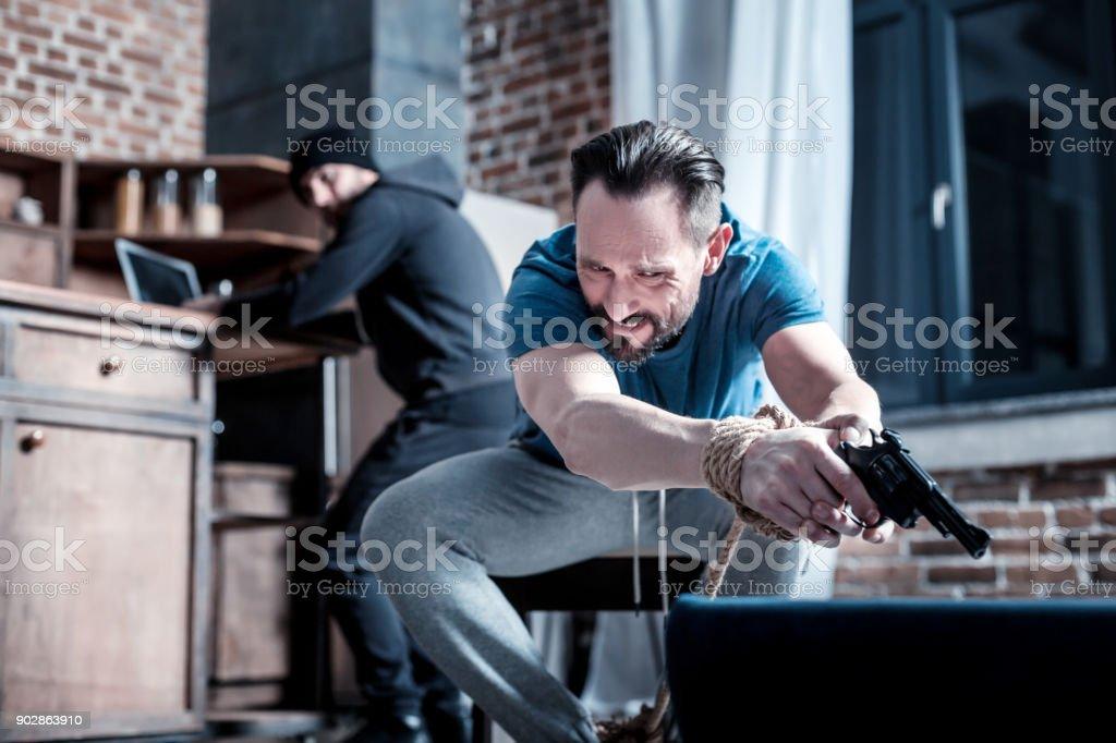 Pânico homem segurar uma pistola com as mãos amarradas - foto de acervo