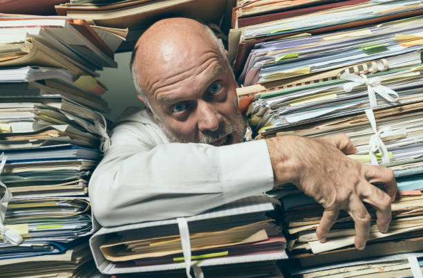 Panicked businessman overloaded with paperwork stock photo
