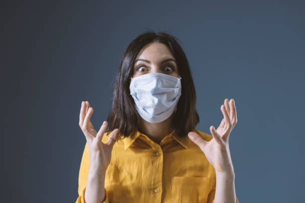 Panicked woman wearing a face mask against covid-19 Panicked woman wearing a face mask against covid-19, she is scared and stressed biological process stock pictures, royalty-free photos & images