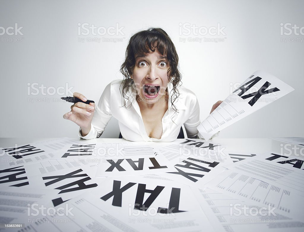 Panicked women screaming over a cluttered pile of tax work stock photo