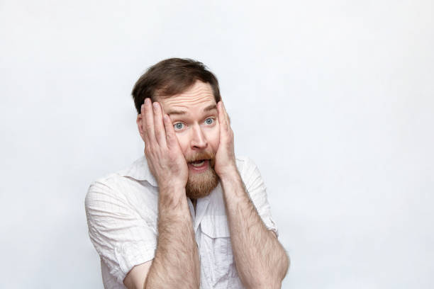 Panicking man holding head in hands over gray background stock photo