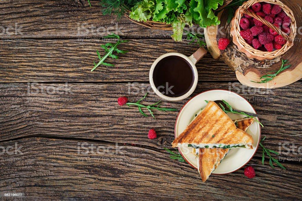 Panini-Sandwich mit Käse und Senf Blätter. Kaffee am Morgen. Dorffrühstück. Ansicht von oben. Flach zu legen – Foto