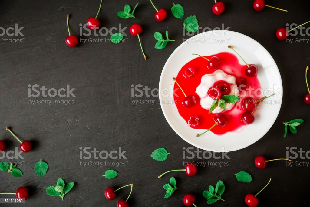 Panna cotta with cherry syrup and berries in plate on a dark background, traditional italian dessert. Flat lay. Top view stock photo