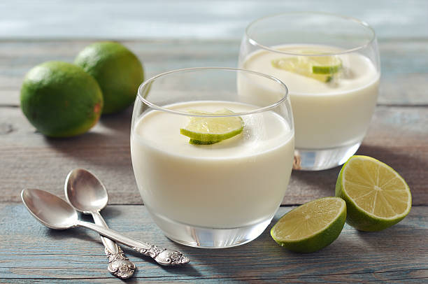 Panna cotta with fresh lime Italian dessert panna cotta with fresh lime in glass on wooden background pudding stock pictures, royalty-free photos & images