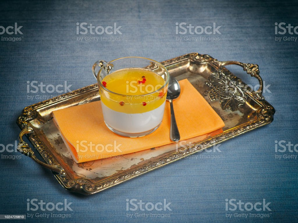 Panna cotta with orange jelly and pink peppercorns stock photo
