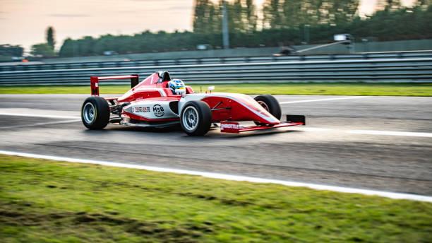 panning shot of a red formula car - formula 1 стоковые фото и изображения