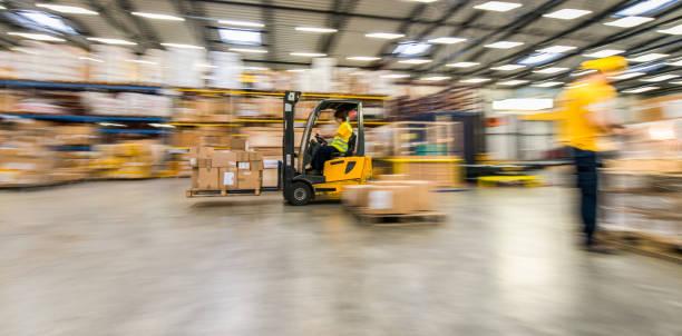 panning shot of moving forklift in a warehouse - caricare attività foto e immagini stock