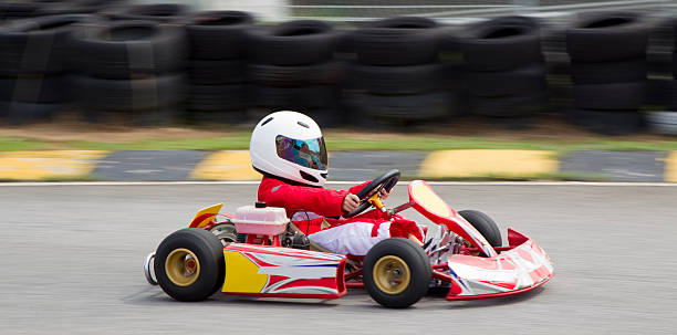 panning shot of young boy in a gokart - young singles stock photos and pictures