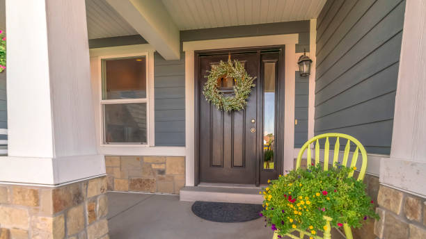 Pano frame Porch and facade of home decorated with colorful flowers and wreath on the door stock photo